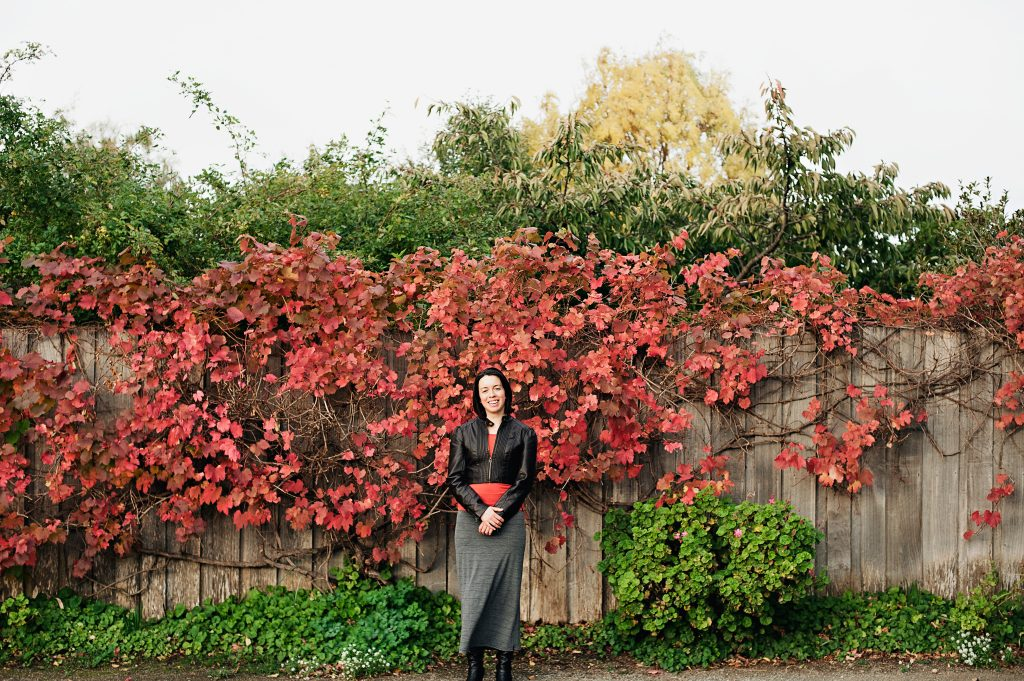 A woman standing in front of a fence with autumn-red leaves